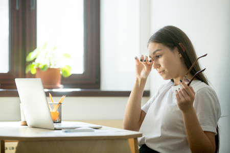 Young female worker with tired eyes holding glasses. Woman feeling discomfort from long wearing eyeglasses behind laptop at workplace. Eyesight strain from computer work concept