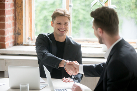 Satisfied entrepreneurs shaking hands after negotiations on meeting in office, two successful businessmen in suits sitting at desk making good deal, happy smiling investor handshaking new partner