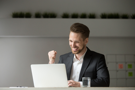 Happy young businessman in suit looking at laptop excited by good news online, lucky successful winner man sitting at office desk raising hand in yes gesture celebrating business success win result Imagens