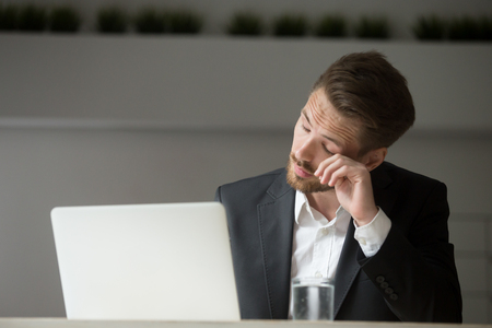 Overworked businessman in suit tired from laptop work, exhausted man feeling lack of sleep, headache or eye strain at workplace, office worker suffering from chronic fatigue after long using computer Stock Photo