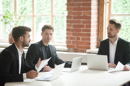 Businessman in suit presenting documents to investors at meeting, man talking convincing clients to make deal or sign contract, three partners negotiating on meeting at conference table with laptops
