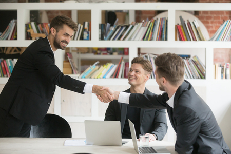 Businessman greeting congratulating new smiling executive team member or making deal with handshake at conference table, friendly company ceo shaking partners hand welcoming at meeting among three