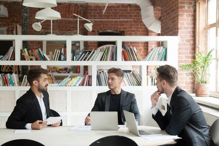 Tres hombres de negocios en trajes discutiendo documentos o estadísticas de proyectos sentados en una reunión ejecutiva en la mesa de la oficina de la conferencia, socios haciendo un nuevo plan de negocios, nuevos inversionistas convenciendo al startupper