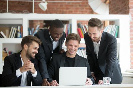 スーツを着た多民族の笑顔のビジネスマンは、一緒にオフィスでラップトップ上で面白い何かを見て、コンピュータ画面上で良いニュースや仕事の