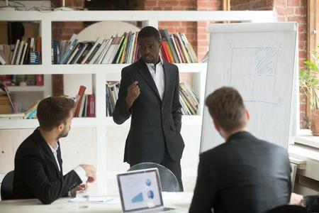 Afroamerikanergeschäftsmann, der den Partnern Darstellung gibt, die mit Flip-Chart bei der Unternehmenssitzung, schwarzer Geschäftstrainer arbeiten, der Projektstrategie unter Verwendung des Whiteboards auf Gruppenbürotraining erklärt