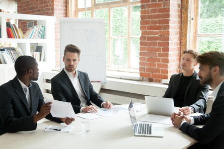 Afro-Amerikaanse adviseur die bedrijfsdocument toont aan investeerders op multi-etnische kantoorvergadering, serieuze diverse zakenmensen in pakken bespreken contractrapport project zittend aan vergadertafel