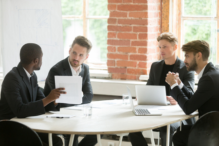 African investment advisor consulting diverse businessmen, partners listening to black consultant holding showing document, making offer, presenting project plan at corporate executive team meeting Banque d'images - 93312274