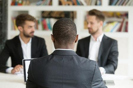 Achteraanzicht op Afrikaanse zakenman tegen twee blanke mannen dragen kostuums, zwarte vacature kandidaat zit zijn rug naar de camera op sollicitatiegesprek met twee werkgevers, HR, collega's of recruiters concept Stockfoto