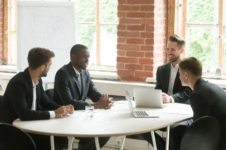 4人の陽気な多様なビジネスマンがミーティングテーブルで笑いながら話し、笑顔で多民族のエグゼクティブグループやパートナーチームが新しいア