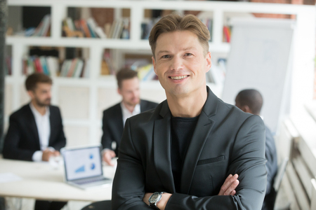 Smiling confident executive in suit standing with arms crossed looking at camera with business partners team at background, happy company ceo co-founder boss board member headshot portrait