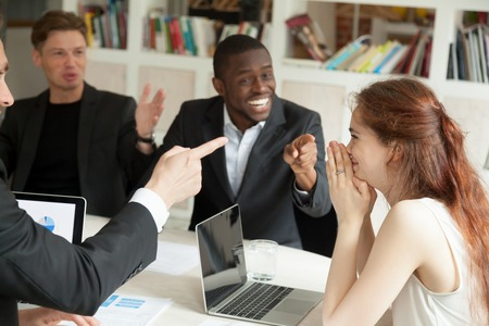 Happy executive businesswoman feels shy at corporate office meeting while male colleagues congratulating supporting success win pointing fingers at coworker, achievement at work, employee recognition