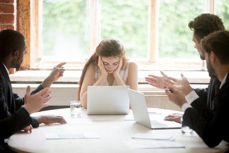 Male colleagues pointing fingers at upset female boss on meeting, tired sad woman leader experiencing gender discrimination at work, businessmen blaming bullying depressed businesswoman for mistake