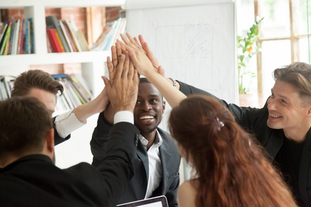 Motivated excited multiracial business team giving high five celebrating corporate growth and financial success, diverse group of colleagues join hands together showing unity help support in teamwork Stock Photo - 93312299