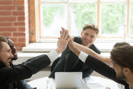 Happy business people giving high five at meeting celebrating success of shared project, diverse motivated executives join hands together, unity help support in teamwork, building successful team Stock Photo - 93312300