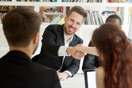 Smiling businessman and businesswoman shaking hands sitting at meeting table, new partners greeting making first impression starting group negotiations teamwork, satisfied entrepreneurs handshaking Stock Photo