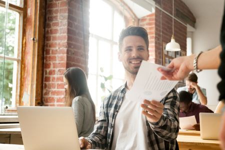 Excited businessman receiving document with financial statistics in office happy about achievement success growth, smiling employee giving project report to executive satisfied with good work result