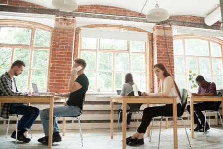 Co-working space concept, diverse people employees working in shared office together, multiracial business men and women sitting at desks using devices in modern loft new coworking interior