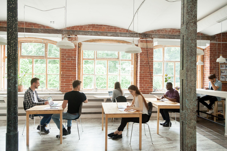 Multiracial people work in modern co-working center interior, diverse employees collaborate sitting at desks of loft shared office, african caucasian colleagues talking in coworking space, teamwork