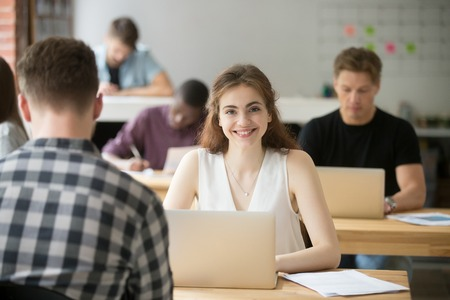 Portrait of smiling attractive woman looking at camera sitting at desk in co-working, young freelancer student intern employee working in shared office, businesswoman with laptop in coworking space