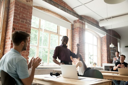 African american team leader performing funny victory dance celebrating achievement in co-working office, black businessman dancing excited by success or win, colleagues supporting clapping hands