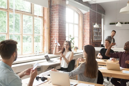 Multiracial corporate team launching paper planes in coworking office interior, diverse employees group laughing having fun at work, lazy workers wasting time, startup concept, career dreams hopes Stock Photo