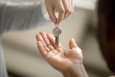 Mujer agente de bienes raíces que da la clave de toma de la mano del cliente afroamericano, hombre negro comprador propietario de la casa que compra una nueva casa, contrato de inversión de préstamo hipotecario, compra de concepto de trato inmobiliario, vista cercana Foto de archivo