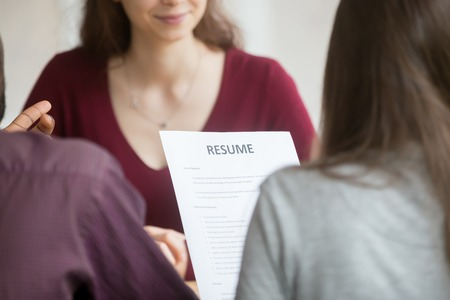 Multiracial hr holding resume at job interview with woman candidate, recruitment team read applicant cv at hiring negotiations concept, human resources recruiters with curriculum vitae, close up view 스톡 콘텐츠
