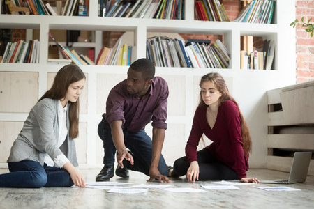 Young multi-ethnic project team brainstorming on office floor, african american leader teaching female managers or designers working together discussing task with laptop and documents, teamwork Stock Photo