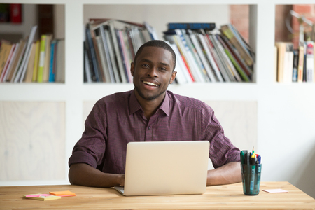 Portrait of friendly attractive african-american businessman entrepreneur sitting at desk with laptop looking at camera, smiling black man business professional posing at workplace with computer