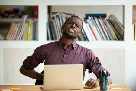 African-american man touching back sitting at desk feeling sudden backache, black businessman suffering from low-back lumbar pain after sedentary work at laptop computer, incorrect posture problems Stock Photo