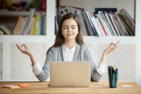 Spokojna kobieta relaksująca medytacja z laptopem, koncepcja bez stresu w pracy, uważna spokojna młoda bizneswoman lub studentka ćwicząca ćwiczenia jogi oddechowej w miejscu pracy, medytacja w biurze