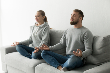 Mindful couple meditating together practicing yoga sitting in lotus pose on sofa at home, calm peaceful man and woman breathing air on couch for keeping mental physical health and emotional balance