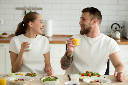 Smiling couple enjoying dinner meal sitting at kitchen table together, husband drinking orange fresh juice smoothie while wife prefers buttermilk yogurt for good digestion, beverage in healthy eating