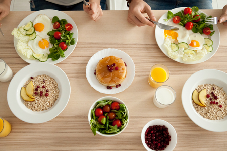 Dining table with food, couple enjoying delicious homemade meal together, man and woman have pancakes, eggs with salad and oatmeal on organic vegetarian breakfast, healthy eating lifestyle, top view Archivio Fotografico