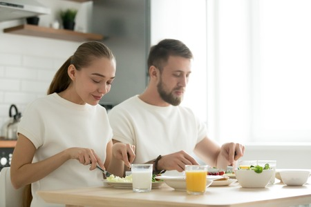 Young happy couple eating with knife and fork together at home, man and woman having dinner at kitchen dining table, tasting healthy balanced delicious yummy breakfast, enjoying organic meal