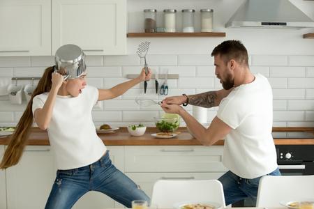 Lustige Paare, die Kampf mit Gerätwerkzeugen beim zusammen zu Hause kochen vortäuschen, der Ehemann und die Frau, die Spaß haben, sich spielerisch zu fühlen, das Küchengeschirr halten, das in der Küche kämpft, die gesundes Lebensmittel zubereitet Standard-Bild