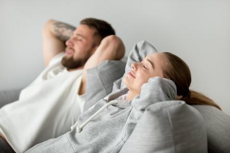 Giovani coppie rilassate che riposano insieme sul sofà comodo a casa, donna felice che sorride respirando aria fresca che si appoggia il cuscino molle di nuovo strato, uomo e donna che godono del pisolino che si rilassa o che medita