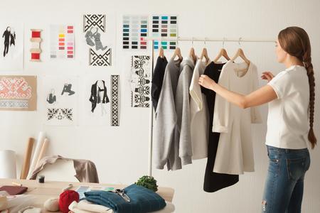 女性のファッションデザイナーは、ファッショナブルなスタイリッシュな手作りの服で衣類ラックの近くに立って居心地の良いワークショップスタ