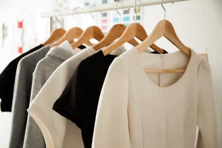 Women dresses new collection of stylish clothes wear hanging on hangers clothing rack rails, fabric samples at background, fashion design studio store concept, dressmaking tailoring sewing workshop