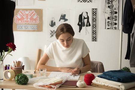 Stilista ispirata alla donna che disegna schizzi con il pennello sul posto di lavoro, la cucitrice lavora nel laboratorio dello studio su nuove idee di raccolta di vestiti, creando un motivo etnico di ricamo a punto croce Archivio Fotografico - 94365007