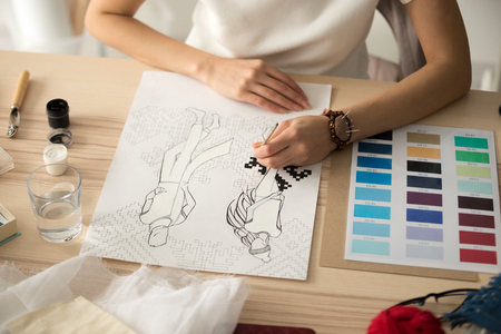 Female hands holding brush painting embroidery pattern scheme on fashion sketch, designer drawing new mens womens wear winter collection sampler at desk with color swatches palette, close up view