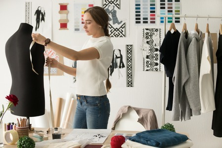 Woman fashion designer measuring mannequin, seamstress holding tape working with dummy in cozy creative design studio or tailor shop, dressmaking and sewing concept, exclusive unique clothes creation Stock Photo