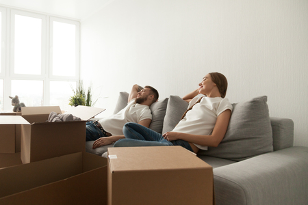 Young couple relaxing on couch just moved into new home with cardboard boxes, man and woman sitting on sofa with belongings in living room ready to move, enjoying moving day and relocation concept