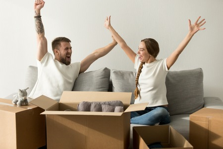 Excited man and woman glad to move in new home, happy house owners raising hands celebrating together with boxes on moving day, married couple achieved goal relocating into own apartment concept Stock Photo