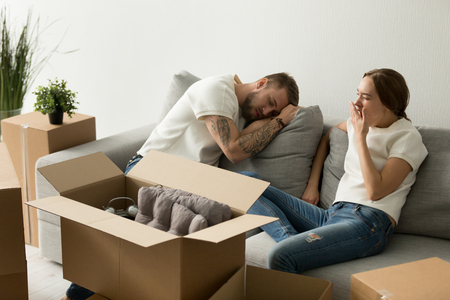 Young tired couple feeling fatigue on long hard moving out day, exhausted restless man having break in new home while sleepy woman yawning on sofa after packing staff in boxes preparing to relocate Banque d'images