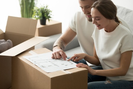 Happy young couple looking at blueprint planning new home interior design settling in, homeowners talking about remodeling ideas, discussing house architectural plan moving in apartment with boxes Stok Fotoğraf