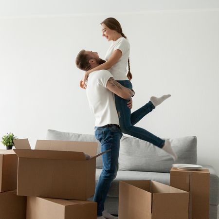 Man lifting woman standing among boxes happy to move into new house, husband holding embracing wife celebrating buying own home, boyfriend and girlfriend enjoying moving day, starting living together Foto de archivo