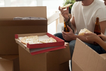 Close up view of couple eating cheese pizza drinking beer celebrating moving day, man and woman having housewarming party together or taking break unpacking boxes in new home, delivery service Zdjęcie Seryjne - 94282567