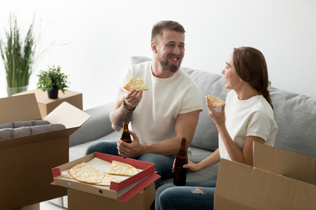 Happy homeowners eating cheese pizza drinking beer having fun together in new home glad to move in own house, young couple celebrating housewarming party taking break from packing unpacking boxes