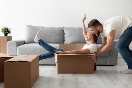 Happy couple having fun laughing moving into new home, young excited woman riding sitting in cardboard box while man pushing it, cheerful roommates playing while packing unpacking belongings together 版權商用圖片